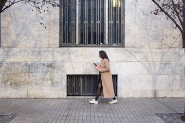 Shot of pretty young woman using her mobile phone while walking in the street.