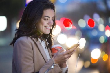 Shot of pretty young woman using her mobile phone while holding cup of coffee in the street at night.