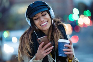 Shot of pretty young woman listening to music with mobile phone while drinking coffee in the street at night.