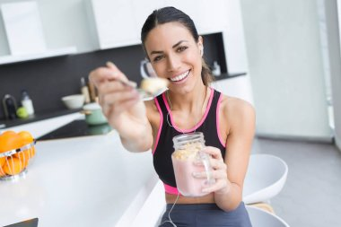 Portrait of sporty young woman showing strawberry smoothie to camera in the kitchen at home.