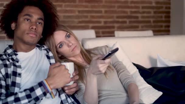 Znuděný mladý pár měnící kanály s dálkovým ovládáním při sledování televize na pohovce doma.