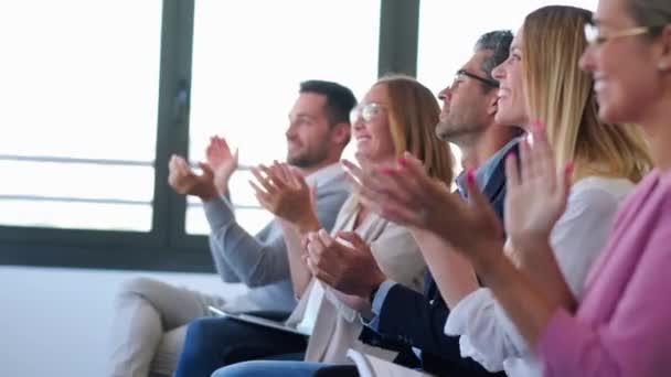 Šťastný obchodní tým, který po poslechu konference tleská a současně sedí na pracovním prostoru.