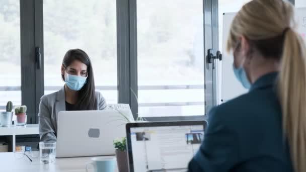 Video dvou obchodních žen s hygienickou obličejovou maskou při práci s notebooky v kooperačním prostoru. Koncept sociálního distancování.