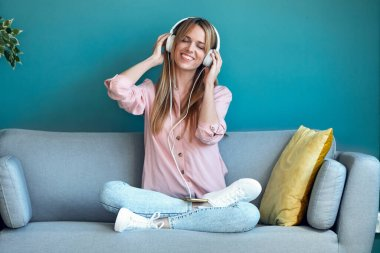 Shot of smiling young woman listening to music with smartphone while sitting on sofa at home.