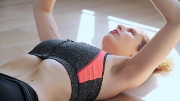 Video atraktivní sportovní mladá žena dělá hypopresivní cvičení v obývacím pokoji doma.