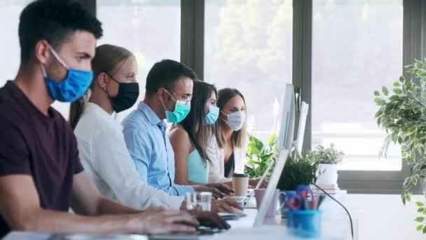 Video úspěšného koncentrovaného obchodního týmu s hygienickou obličejovou maskou při společné práci v kanceláři při udržování bezpečné vzdálenosti na pracovišti.