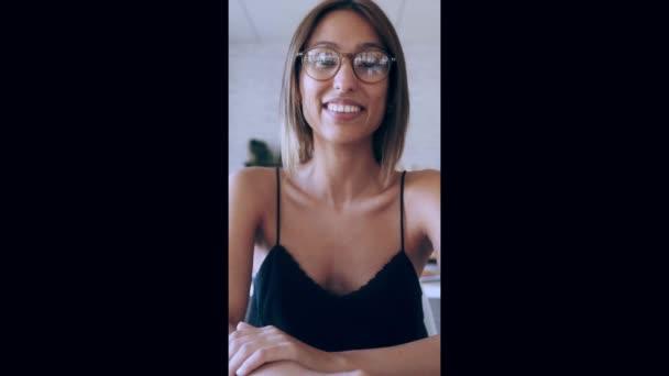 Video der schönen lächelnden Geschäftsfrau, die durch eine Smartphone-Webcam schaut und spricht, während sie eine Videokonferenz von ihrem Start-up-Kleinunternehmen macht.