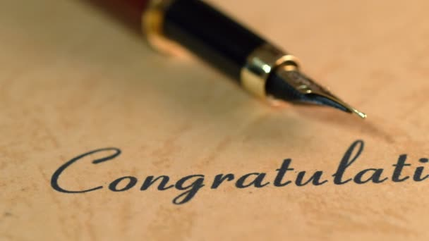 Fountain pen on congratulations text