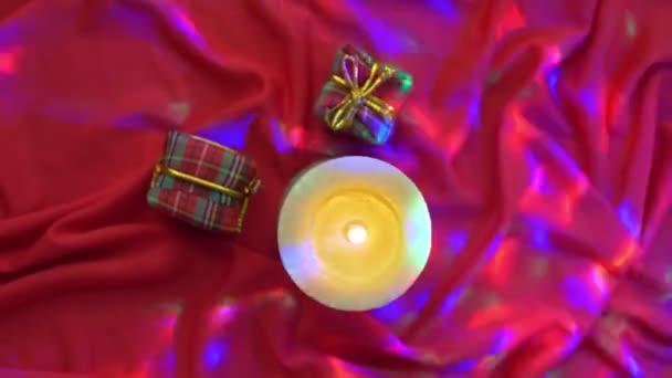 Červené současné krabic na hedvábné pozadí se světly a svíčka