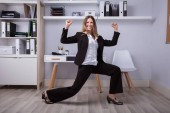 Fotografie Side View Of A Happy Businesswoman Doing Stretching Exercise In Office