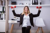 Portrait Of A Smiling Businesswoman Doing Exercise With Dumbbell