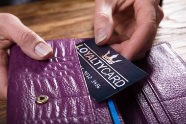 Close-up Of A Businessperson's Hand Removing Loyalty Card From Purse