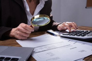 Businessperson's Hand Analyzing Invoice Through Magnifying Glass In Office