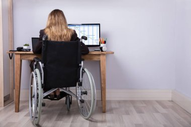 Rear View Of A Disabled Businesswoman Sitting On Wheelchair Working On Computer