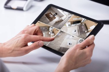 Close-up Of A Person's Hand Monitoring CCTV Footage On Digital Tablet