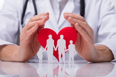 Close-up Of A Doctor's Hand Protecting Family Cut Out With Red Heart Shape