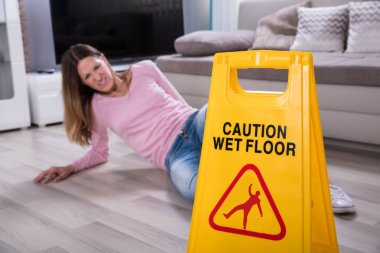 Mature Woman Falling On Wet Floor In Front Of Caution Sign At Home