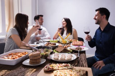 Smiling Young Friends Enjoying Food With Glass Of Wine At Restaurant