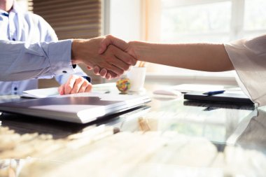 Close-up Of Two Business Partners Shaking Hands Over Desk In Office stock vector