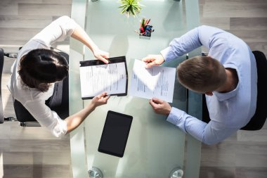 Elevated View Of Two Businesspeople Holding Resume Over Desk In Office