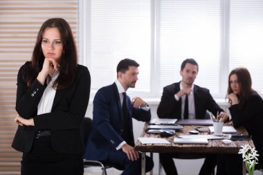 Portrait Of A Sad Businesswoman In Front Of Her Colleagues Sitting In Office