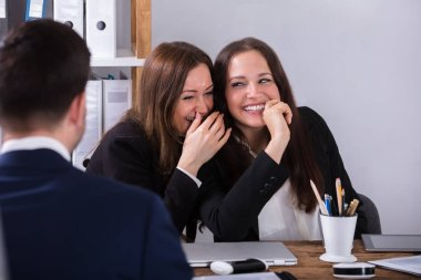 Two Happy Young Businesswoman Gossiping About Male Colleague At Workplace