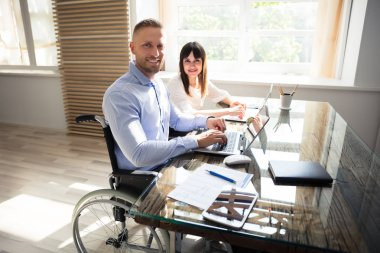 Portrait Of Smiling Disabled Businessman With His Colleague Working On Laptop