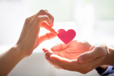 Close-up Of Woman Giving Red Heart On Man's Hand