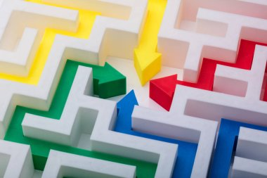 Elevated View Of Multi Colored Arrows In The Centre Of White Maze