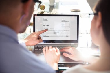 Close-up Of Two Businesspeople Analyzing Invoice On Laptop