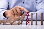 Fotografie Humans Finger Over Risk Word Stopping Dominos From Falling On Desk