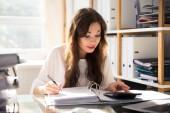 Junge Geschäftsfrau berechnet Rechnung mit Rechner im Büro