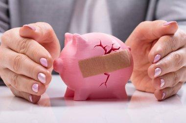 Businesswoman's Hand Protecting Broken Piggybank With Bandage