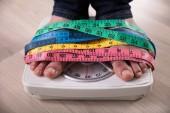 Közeli kép: A személy lábát kilogramm skála, csomagolva több színű mérőszalag