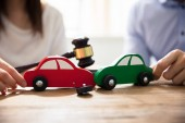 Couple Holding Red And Green Car In Front Of Gavel