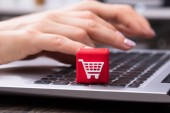 Human Hand Using Laptop With Red Cubic Block Showing Shopping Cart Icon