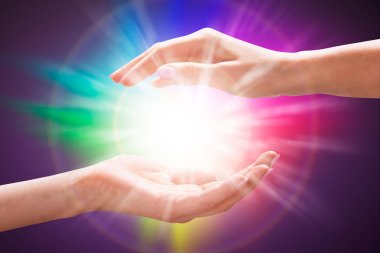 Close-up Of A Woman's Hand Holding Light Against Colorful Background