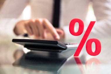 Close-up Of A Percentage Sign Near Businessperson's Hand Using Calculator On Desk