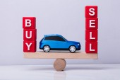 Fotografie Blue Car Between And Buy And Sell Cubic Blocks Balancing On Wooden Seesaw