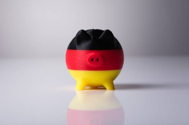 Close-up Of Piggybank Painted With German Flag On Reflective Background