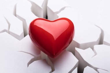 Kırık beyaz zemin üzerine kırmızı kalp yüksek açılı görünüş