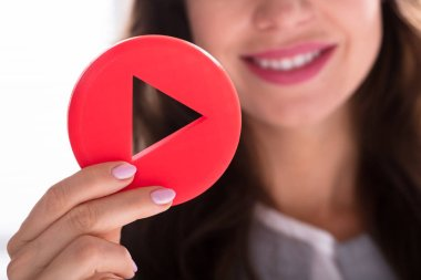 Close-up Of A Businesswoman's Hand Holding Red Play Button