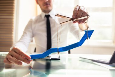 Businessperson's Hand Manipulating Blue Arrow With Rope