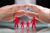 Nahaufnahme der Hand eines Geschäftsmannes, der rote Familienfiguren schützt