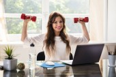 Smiling Young Businesswoman Exercising With Red Dumbbells