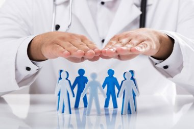 Doctor's hand shielding human figures forming circle