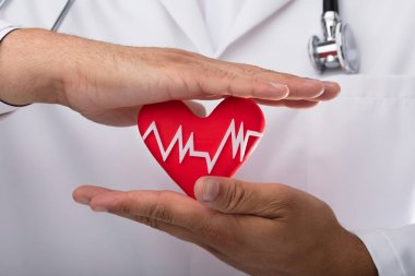 Close-up of a doctor's hand holding red heart rate