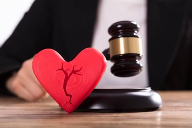 Close-up Of A Broken Red Heart In Front Of Judge Striking Mallet