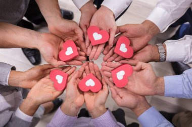 High Angle View Of Businesspeople Holding Red Hearts