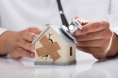 Fotografie Doctors hand examining broken house with stethoscope on reflective desk